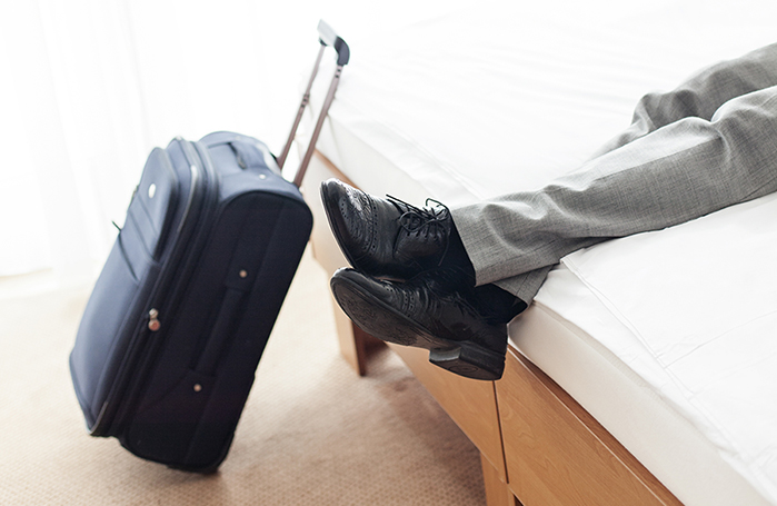 Section Of Businessman Relaxing On Bed By Luggage In Hotel Room